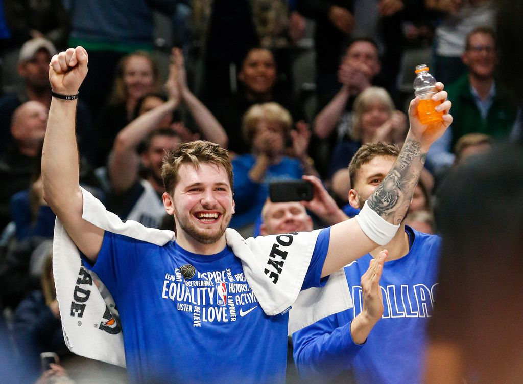 Dallas Mavericks guard Luka Doncic (77) celebrates as center Boban Marjanovic (51) breaks free the ball, which was lodge between backboard cameras, during the second half of an NBA matchup between the Dallas Mavericks and the Sacramento Kings on Wednesday, Feb. 12, 2020 at American Airlines Center in Dallas.