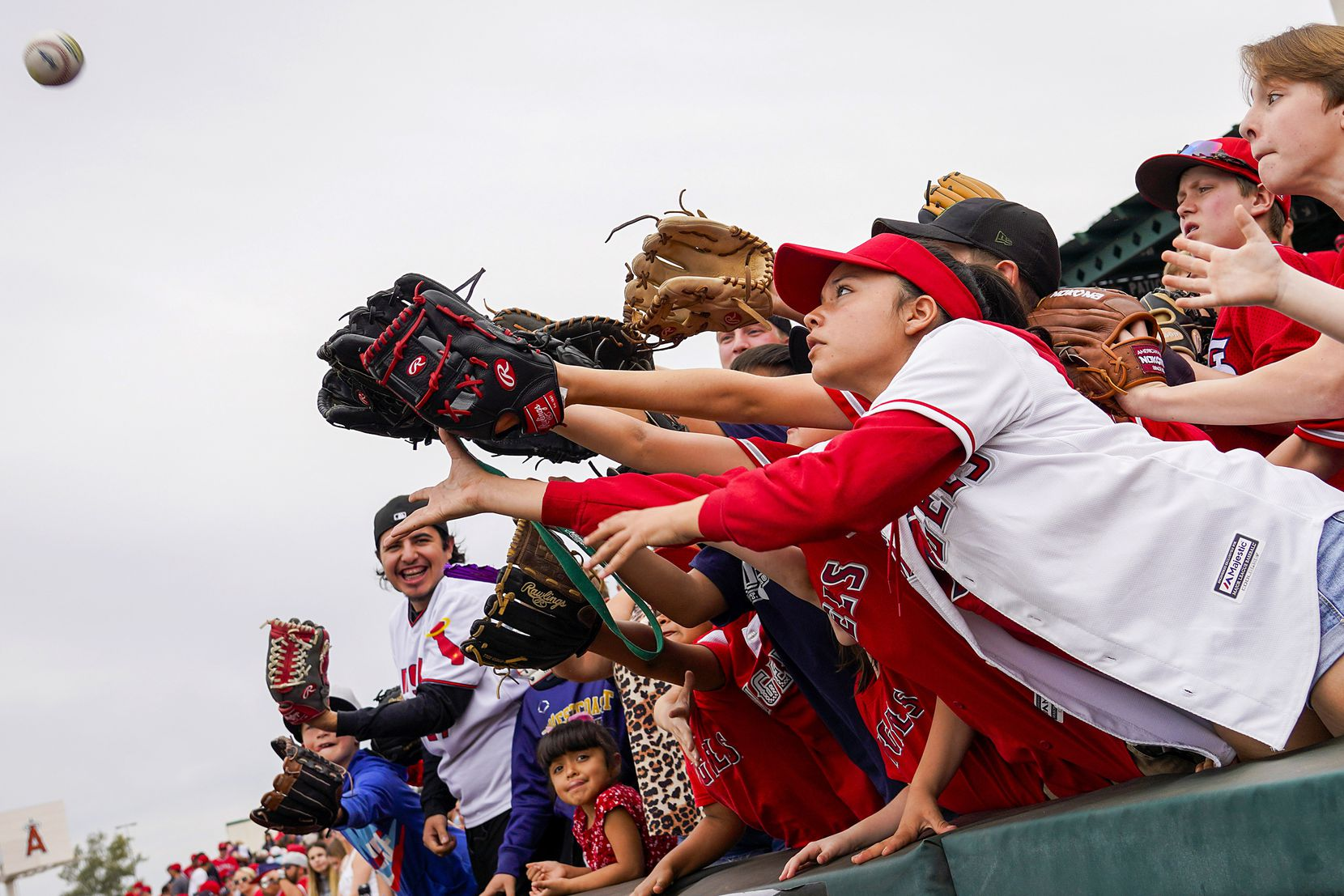 Young fans reach for a ball tossed into the stands by Los Angeles Angels first baseman Albert Pujols during the fifth inning of a spring training game against the Texas Rangers at Tempe Diablo Stadium on Friday, Feb. 28, 2020, in Tempe, Ariz.