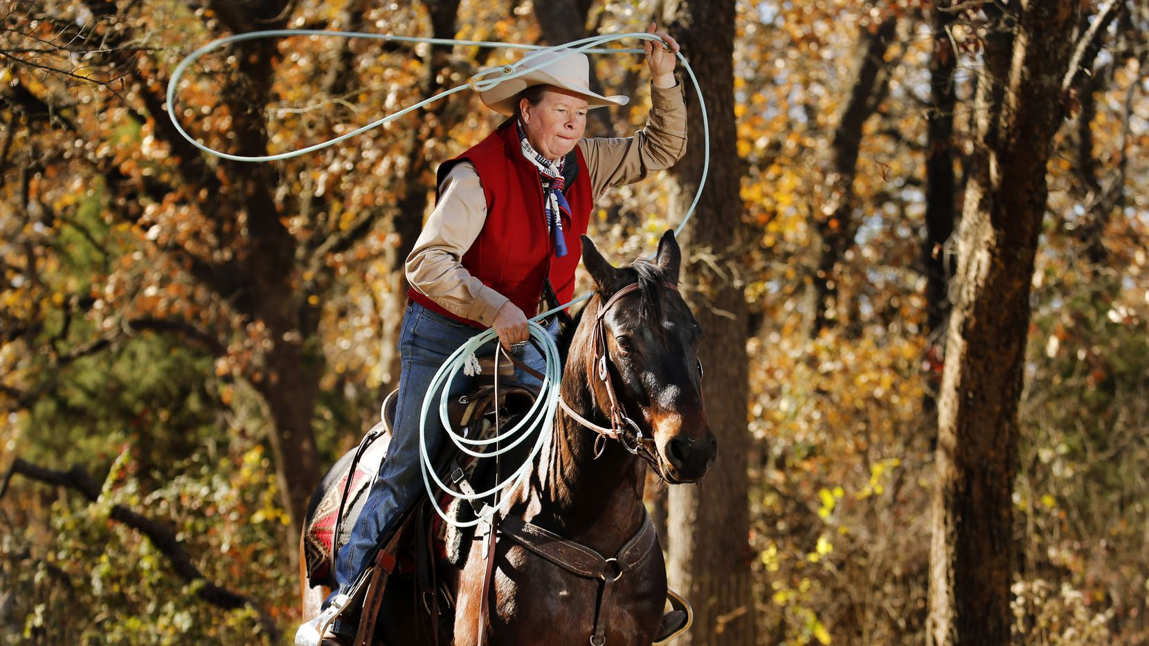 Teacher Gay Leigh Bingham retired this fall rather than face the health risks and disruptions of the coronavirus. She was practicing roping on her horse, Mikey, at her Broken Bow Ranch in Seagoville, where she offers trail rides and riding lessons to supplement her retirement income.