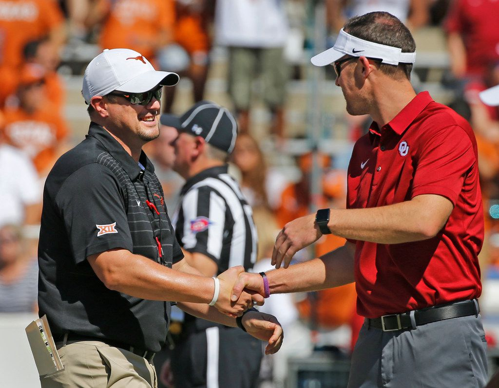 FILE - Texas head coach Tom Herman and Oklahoma head coach Lincoln Riley shake hands before the Oklahoma University Sooners vs. the University of Texas Longhorns NCAA college football game at the Cotton Bowl in Dallas on Saturday, October 14, 2017. (Louis DeLuca/The Dallas Morning News)