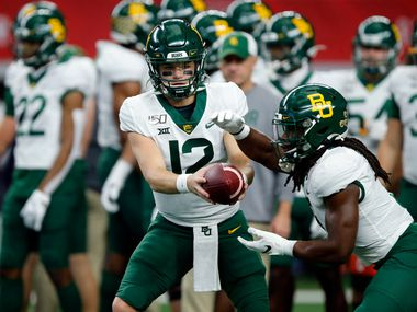 Baylor Bears quarterback Charlie Brewer (12) hands the ball off to running back JaMycal Hasty (6) during warm ups before facing the Oklahoma Sooners in the Big 12 Championship at AT&T Stadium in Arlington, Saturday, December 7, 2019.