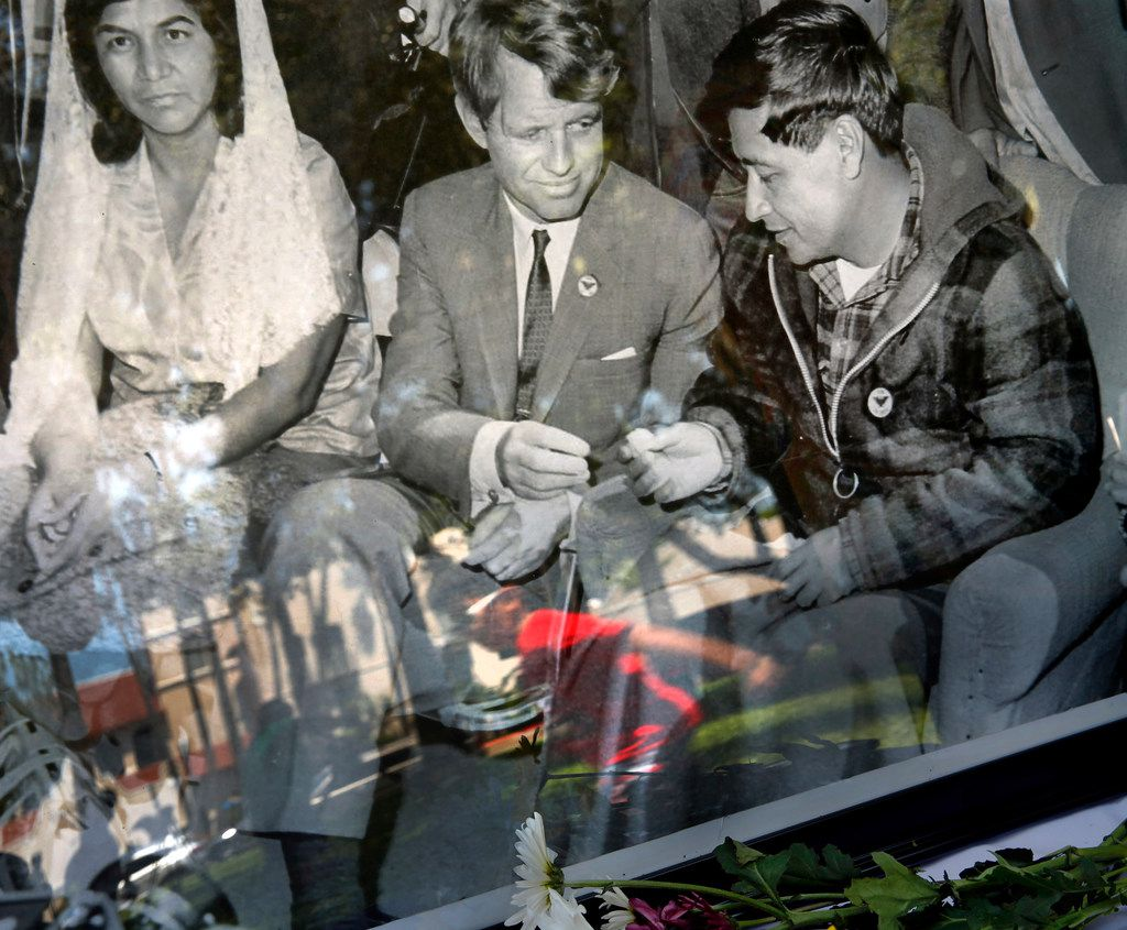 A child is reflected racing past a black and white photo of Robert F. Kennedy and civil rights activist Cesar Chavez (right) during a Break Bread Not Families rally at Archer Park in McAllen, Texas, Saturday, June 23, 2018. Robert's daughter and activist Kerry Kennedy spoke at the rally hosted by LUPE (La Union Del Pueblo Entero).