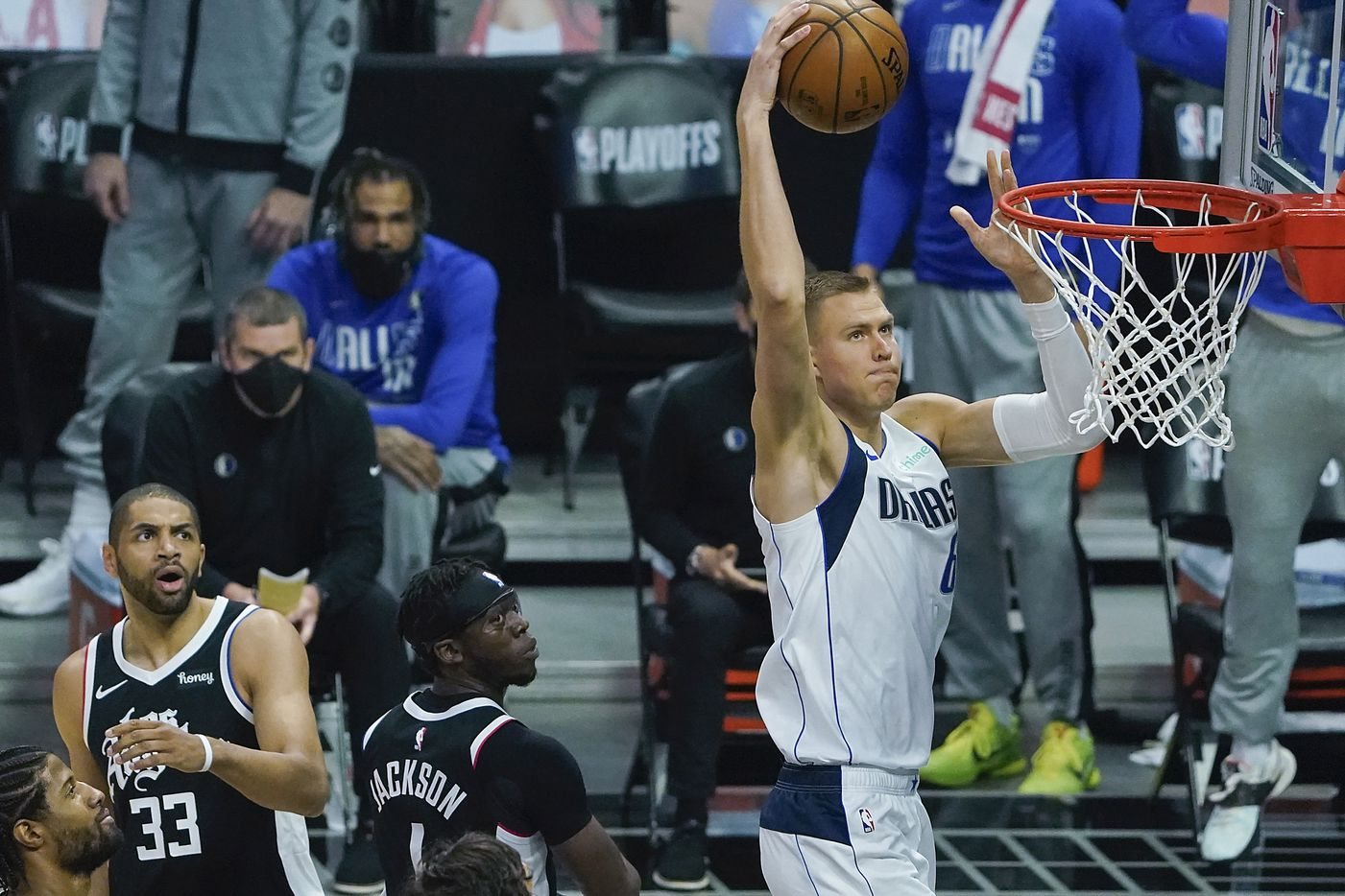 Dallas Mavericks center Kristaps Porzingis (6) goes up for a dunk past LA Clippers guard Reggie Jackson (1) and forward Nicolas Batum (33) during the first quarter an NBA playoff basketball game at the Staples Center on Wednesday, June 2, 2021, in Los Angeles.  (Smiley N. Pool/The Dallas Morning News)