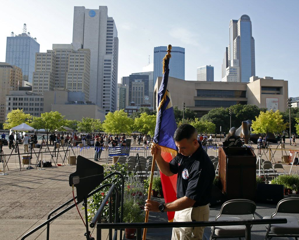 Dallas police officer Peter Lickwar sets up the Texas flag before a candlelight vigil hosted by the Dallas Police Association at Dallas City Hall in Dallas, TX July 11, 2016. (Nathan Hunsinger/The Dallas Morning News)