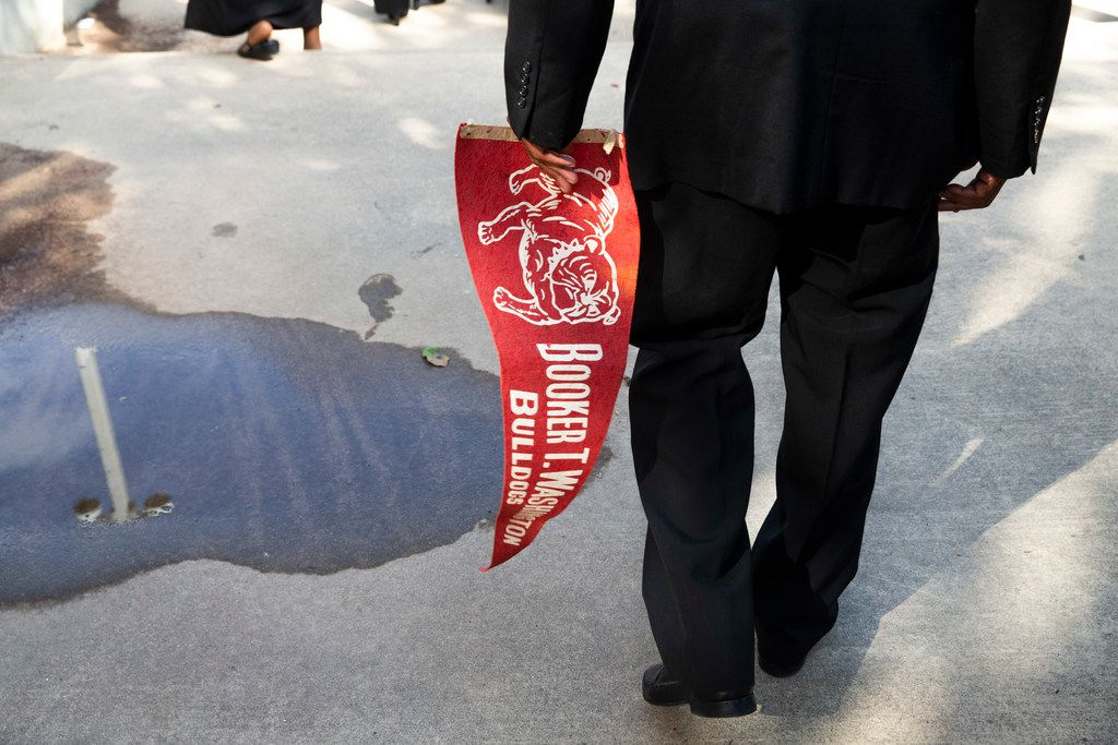 Glenn Bragg carries his Booker T. Washington school pennant following ceremonies honoring members of the class of 1969  at Booker T. Washington High School for the Performing and Visual Arts in Dallas on Sunday, June 2, 2019. Fifty years after desegregation separated classmates at Booker T. Washington Technical High School, the class of 1969 turned its reunion Sunday into a belated convocation. Some members of the Class of '69  were unable to graduate from Booker T. Technical High School when a federal desegregation order dispersed them to other Dallas high schools. The ceremony also honored students who would have graduated in 1970 had officials not closed the school. (Shaban Athuman/Staff Photographer)