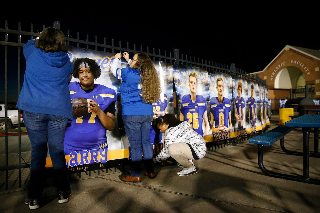 Candace Brown (center) and her mother Teresa Brown (left) hang a photo of her son and senior football player Larry Hall onto a fence at Community ISD Stadium in Nevada, Texas, Friday, November 8, 2019. Larry's sister Bailee Brown (right) helps out on Senior Night. (Tom Fox/The Dallas Morning News)