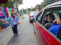 Kathy Bennett (left) asks participants to choose a box during the Opening Day of the Big Tex Fair Food Drive-Thru at Fair Park in Dallas Friday, Sept. 25, 2020. On Saturday, Sept. 26, twice as many cars entered the grounds, and attendees waited for hours to get into the fairgrounds.