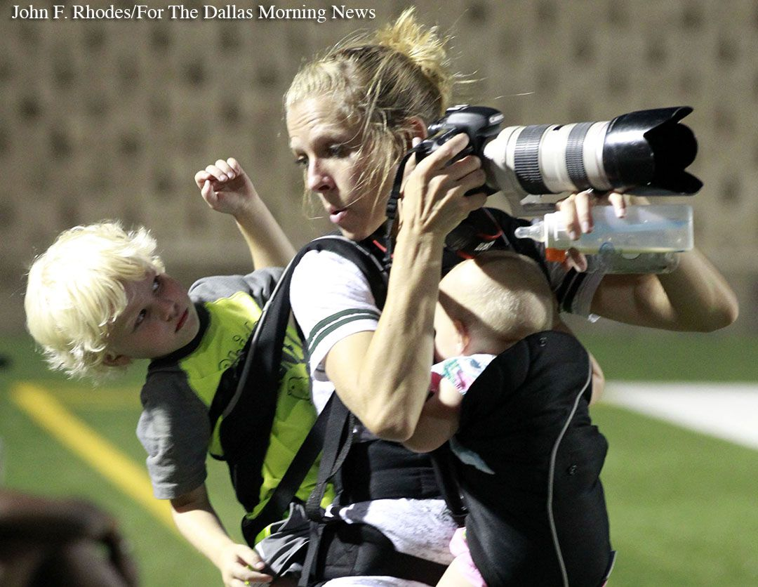 Photographer Melissa Wardlow multitasks, by talking with three-year-old son Jordan, and feeding eight-month-old Addison, while photographing the first half of a high school football game between Mansfield Lake Ridge and Mesquite Poteet High on Friday, September 9, 2016. Barlow is the wife of a Lake Ridge coach, who also shoots photos for the team.