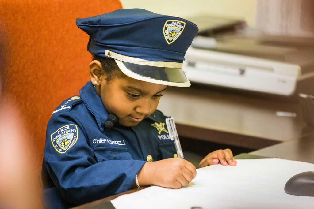 Ah'Maya draws on a piece of paper in a patrol office during a tour of the Cedar Hill Police Department.