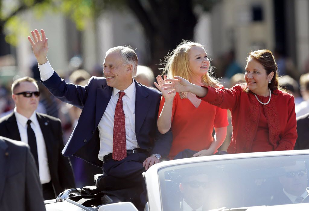 Texas Gov. Greg Abbott, left, with daughter Audrey, center, and wife, Cecilia, waves during an inauguration parade, Tuesday, Jan. 20, 2015, in Austin, Texas.