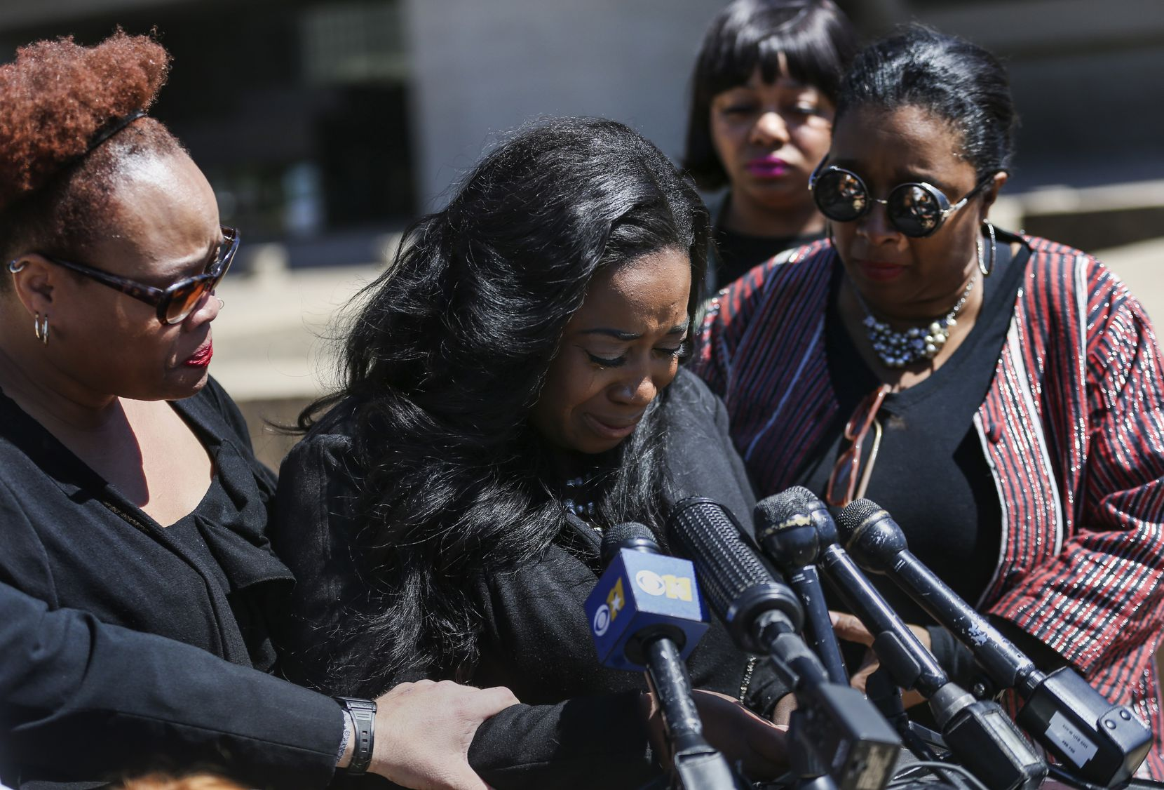 Supporters surround Keyaira Saunders as she speaks during a news conference at Dallas City Hall on April 19.