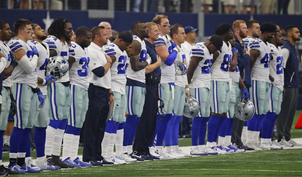 Dallas Cowboys head coach Jason Garrett, with Dez Bryant and Jason Witten on either side of him, stands for the national anthem before a game against the Los Angeles Rams on Sunday, Oct. 1, 2017 in Arlington, Texas. (Paul Moseley/Fort Worth Star-Telegram/TNS)
