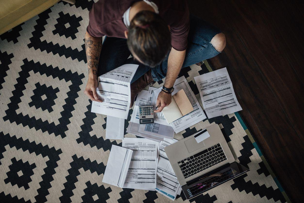 Una mujer reconcilia sus pagos pendientes en su computadora.