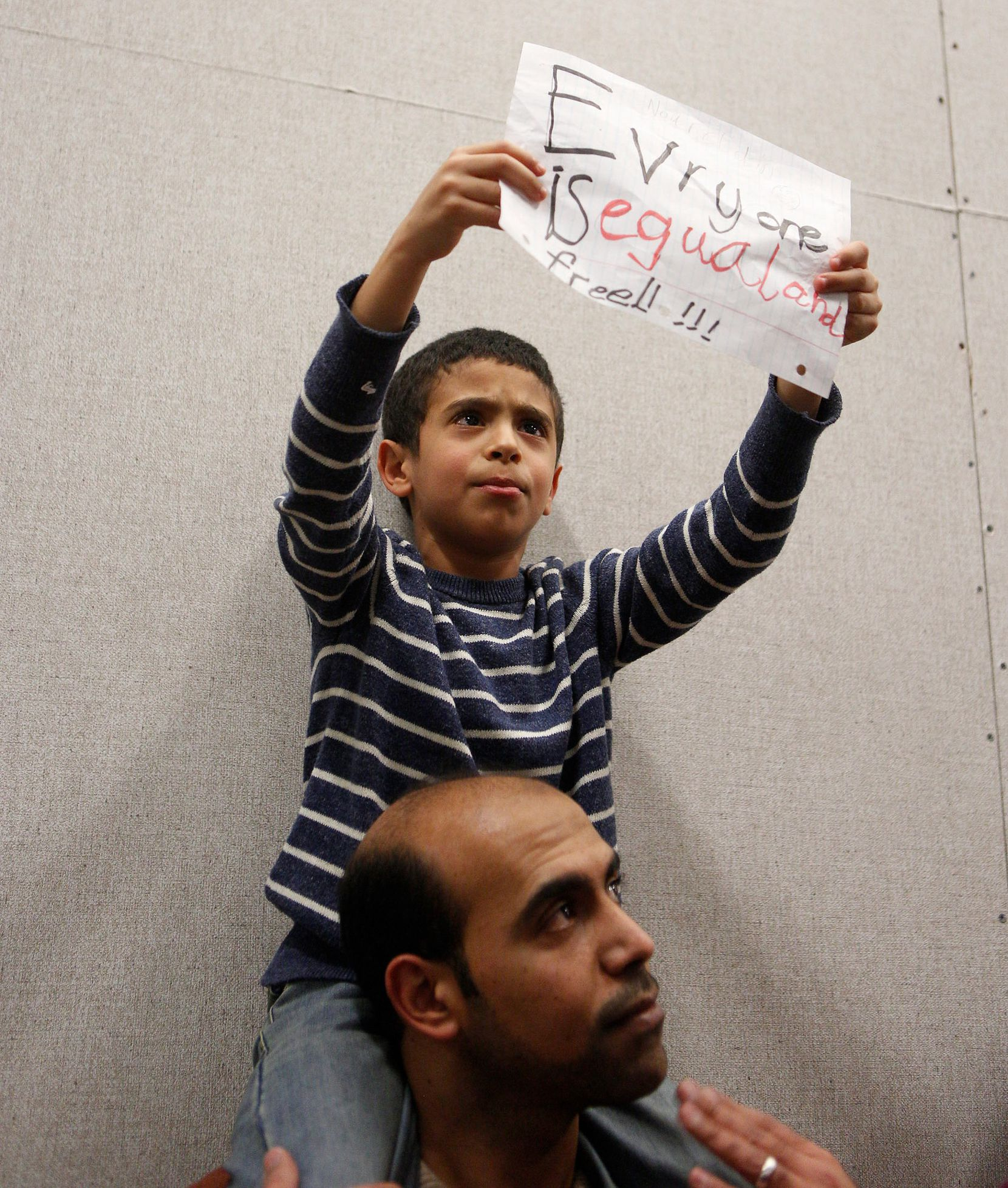 Mahmoud and his son Nour, 7, join the protest to denounce President Donald Trump's executive order that bans certain immigration, at Dallas-Fort Worth International Airport on January 28, 2017 in Dallas, Texas.