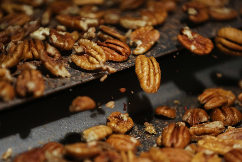 Inspectors look for insect bites, discolorations and remaining shell while examining pecans inside Navarro Pecan Company in Corsicana, Texas Friday October 27, 2017. Navarro Pecan Company is one of the largest pecan producers in the world and was founded in 1977. The pecan is the only commercially produced nut that is native to America. Navarro only uses pecans grown in America. (Andy Jacobsohn/The Dallas Morning News)