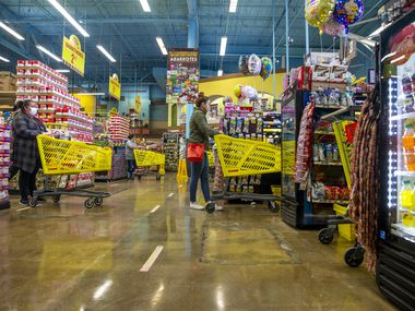 Customers waiting to check out stand six feet apart at the El Rancho Supermercado on Gaston Avenue in Dallas. The store began taking precautionary measures against the spread of COVID-19 two weeks ago, and store manager Eugenio Osorio said measures include employees having their temperature checked before each shift, a power wash of the outside entrance every twenty minutes, and an employee monitoring a one-in, one-out customer entrance policy.