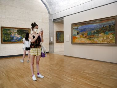 Libby Krueger of Fort Worth takes a photo of paintings in the Kimbell Art Museum as her friend Kimberly Brubacher of Los Angeles views one of Claude Monet's water lily paintings. The Fort Worth museum is now open after its shutdown early in the coronavirus pandemic.