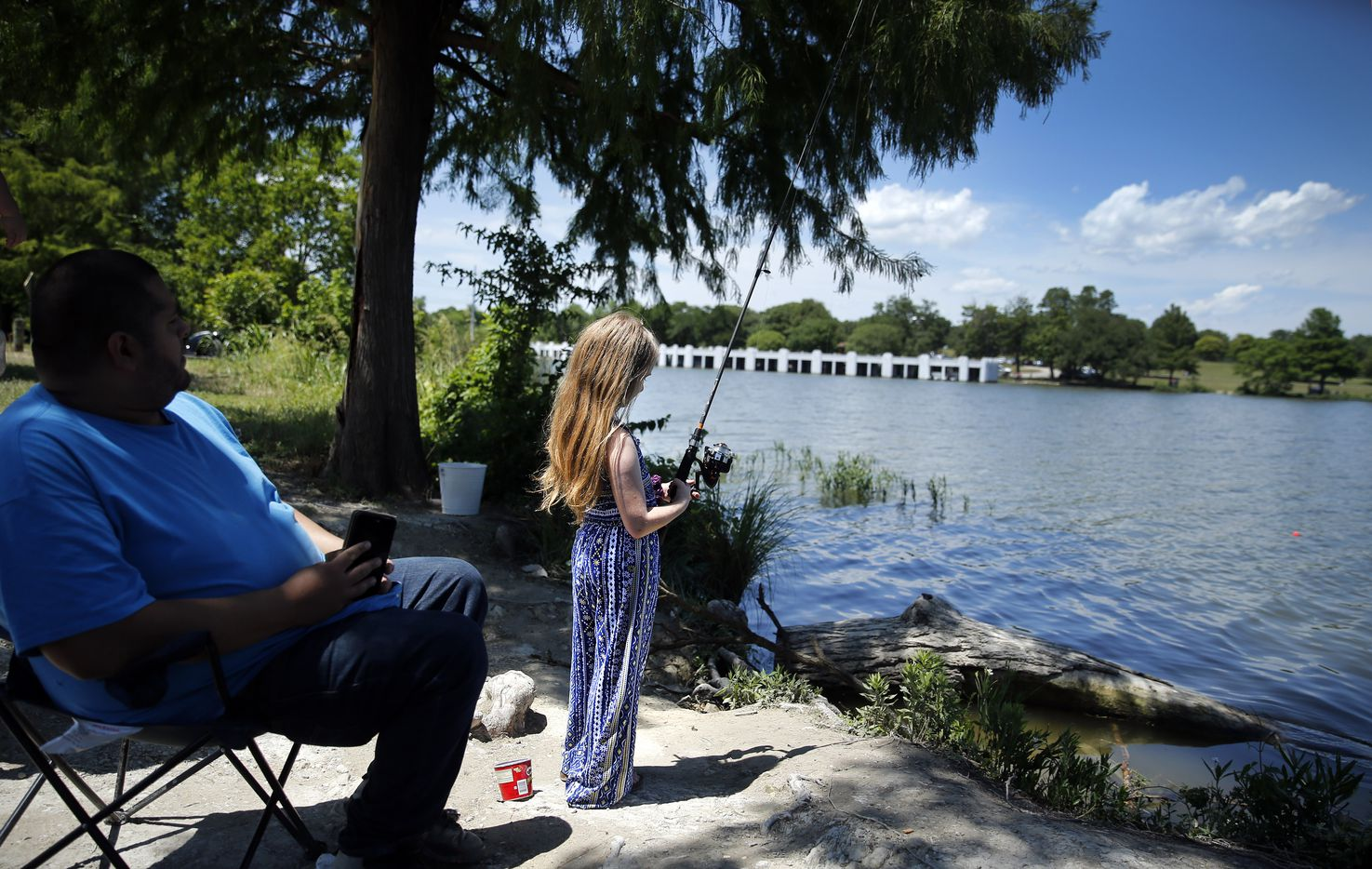 Aubrey Lawrence, 8, watches her bobber as she fishes with her family at White Rock Lake.