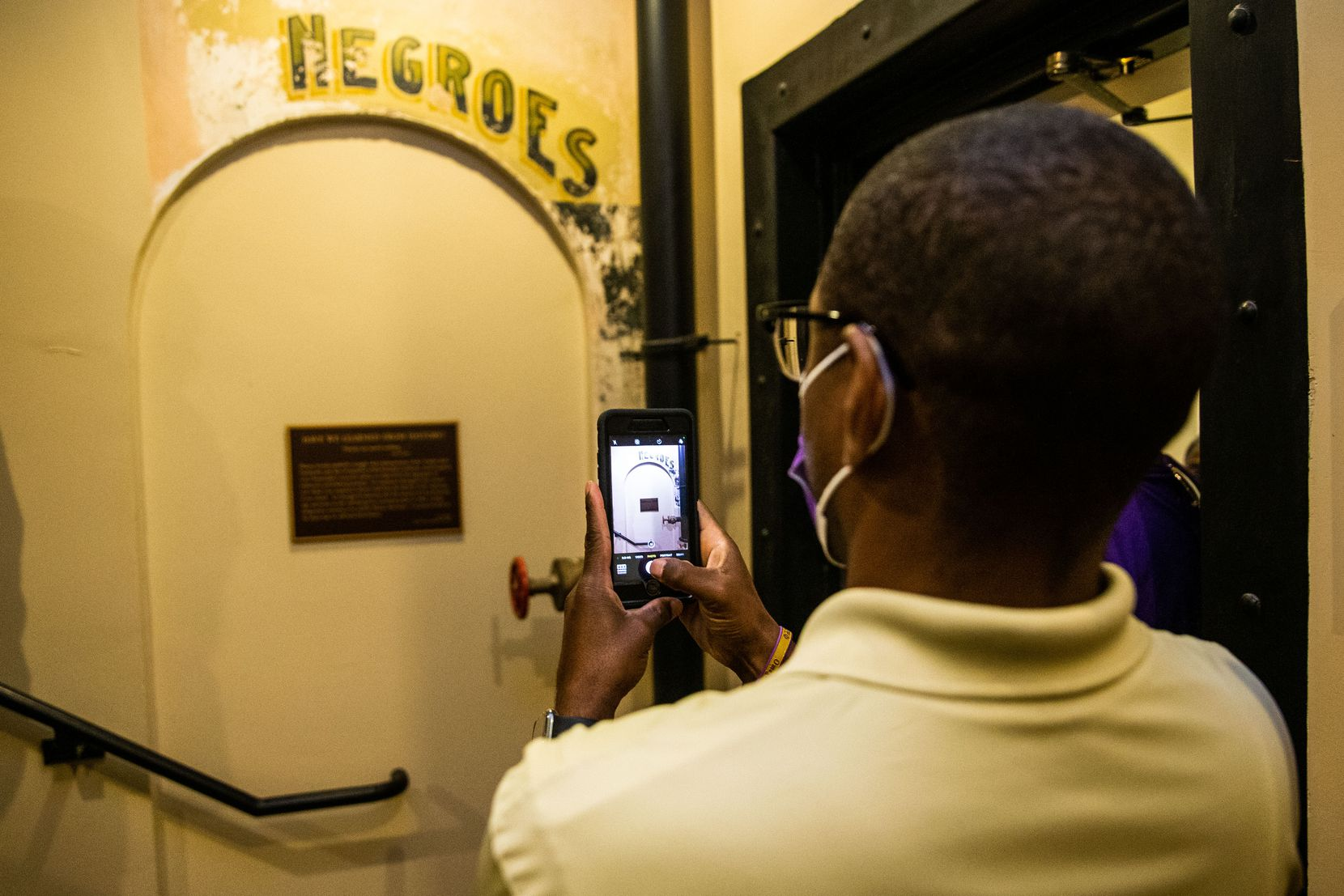 """Dannion McLendon takes a photo of the historical marker and sign that reads """"NEGROES"""" at the Ellis County Courthouse in Waxahachie."""