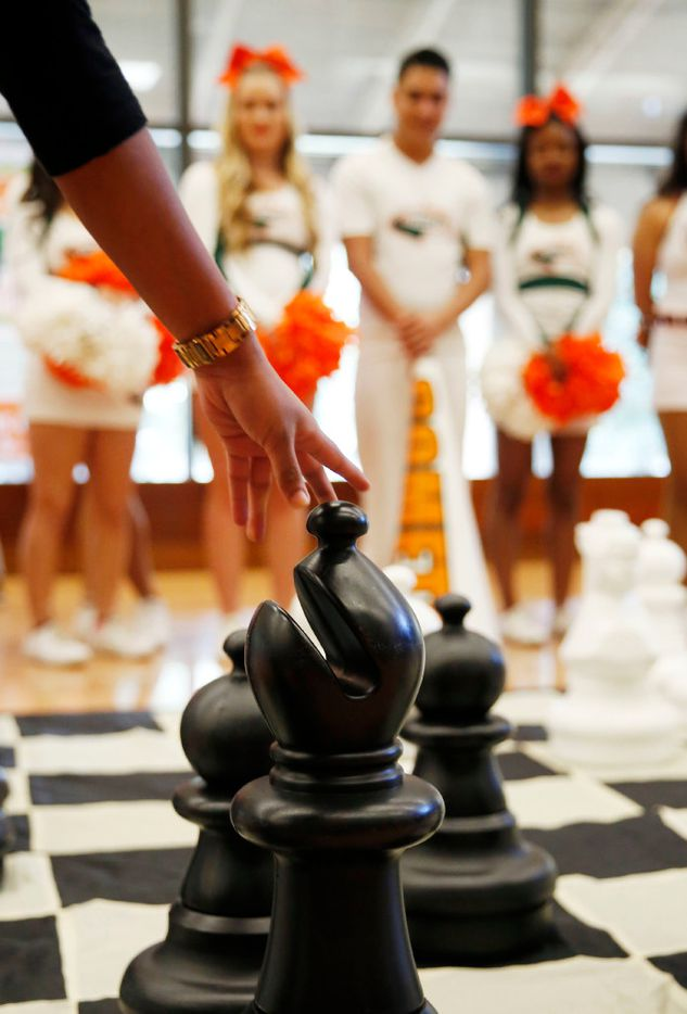 Student Deepthi Savulgay plays larger-than-life chess during a campus pep rally for the University of Texas at Dallas chess team in Richardson on Wednesday.