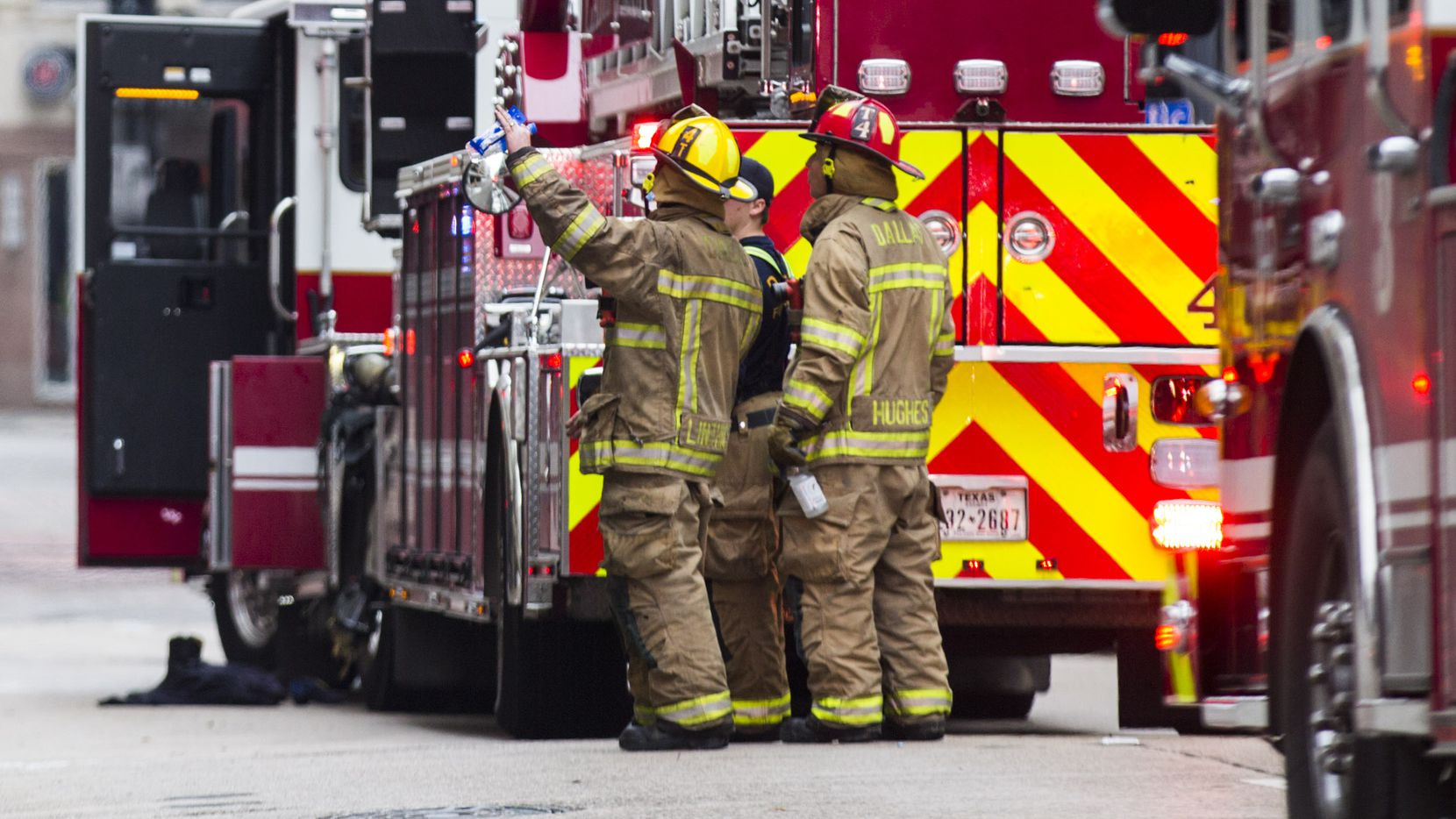 Fire fighters stand outside of Zenna Thai & Japanese Restaurant after fighting a fire that started in the kitchen on Thursday, February 28, 2019 in downtown Dallas.