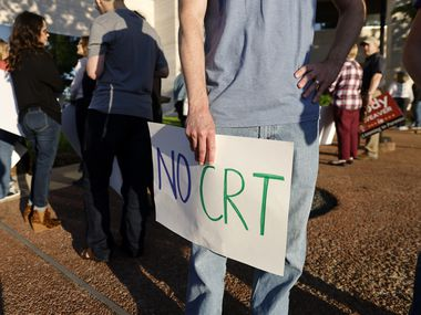 Michael Woodmansee brought a 'No CRT' sign to show concern about critical race theory being taught in schools during a heated debate about diversity and inclusion at Plano ISD's board meeting on May 4.