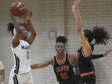 Arlington Martin's Mariah Roberts (5) passes over the defense of South Grand Prairie's Kiara Jackson (3) during second half action. The two teams played their District 8-6A  girls varsity basketball game at Arlington Martin High School in Arlington on January 26, 2021. (Steve Hamm/ Special Contributor)