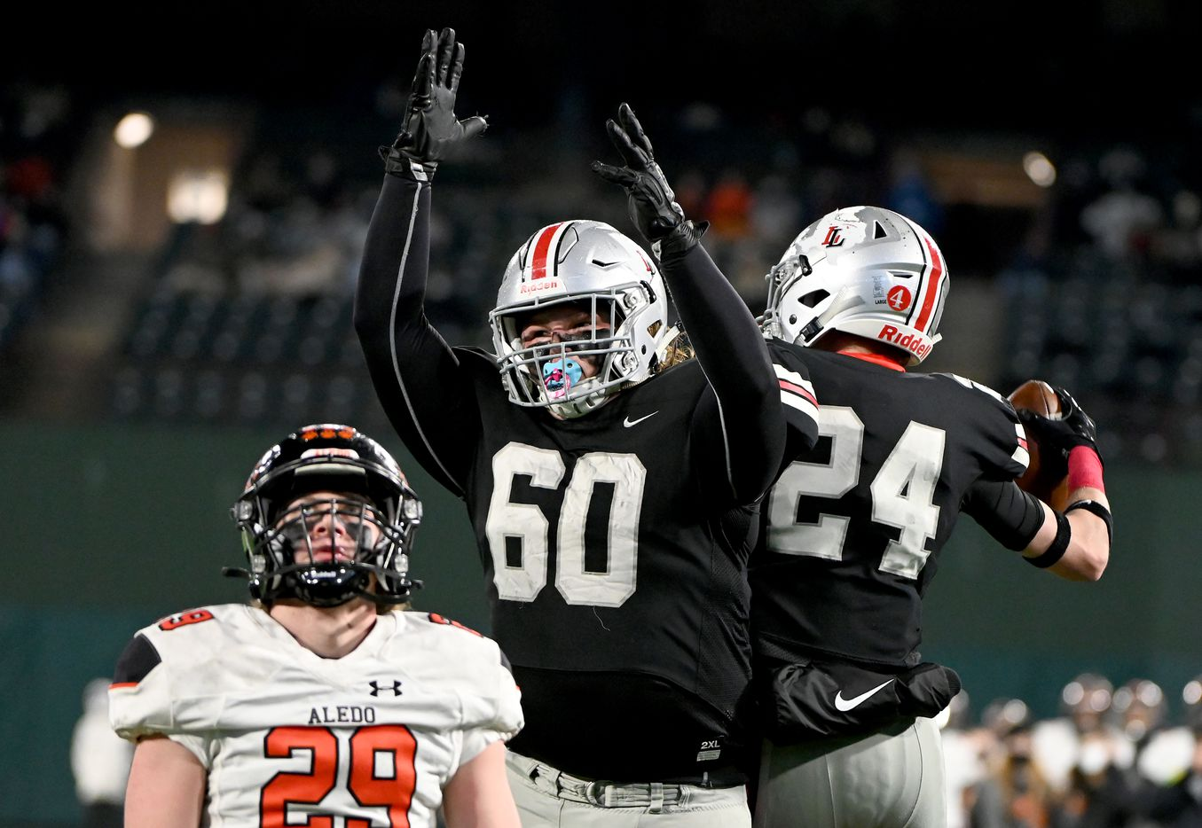 Lovejouy's Trent Robinson (60) celebrates with Trent Rucker (24) after Rucker's touchdown catch in the second quarter of the Class 5A Division II Region II final high school football game between Aledo and Lovejoy, Friday, Jan. 1, 2021, in Arlington, Texas. (Matt Strasen/Special Contributor)