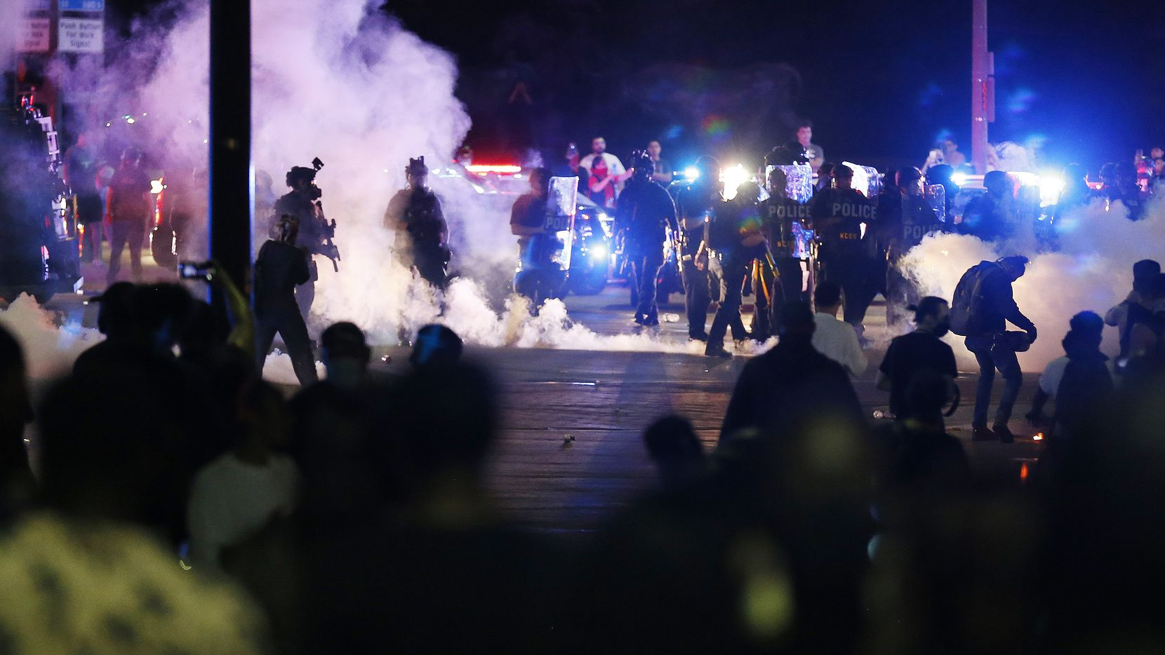 Dallas police attempt to disperse the crowd of protesters along Young Street and Griffin in downtown Dallas on Friday. After peaceful demonstrations led to late-night looting in several cities over the weekend, some blamed outside forces for causing trouble.