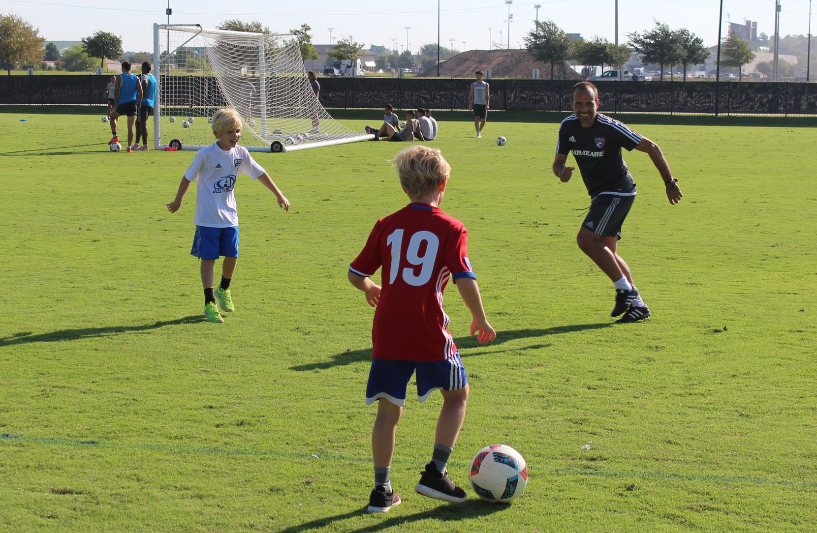 FC Dallas head coach, Oscar Pareja (right), plays soccer with the sons of Bobby Rhine, Miller (left) and Jake (center)
