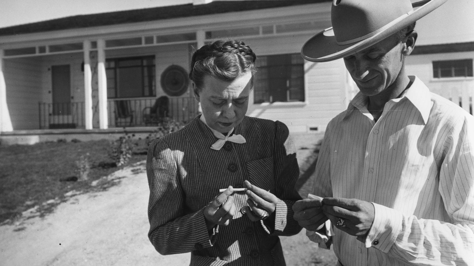 Jerry (left) and Ernie Pyle rolling cigarettes in front of their home. Ernie was home on a rare break as a war columnist during World War II. 1944. Courtesy of the Palace of the Governors Photo Archives, 183255.