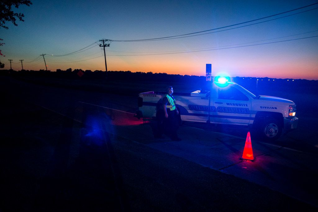 Officials block a road where one student died when a Mesquite ISD school bus rolled into a ditch with 40 students on board in Mesquite, Texas on Wednesday, October 3, 2018.  (Shaban Athuman/The Dallas Morning News)