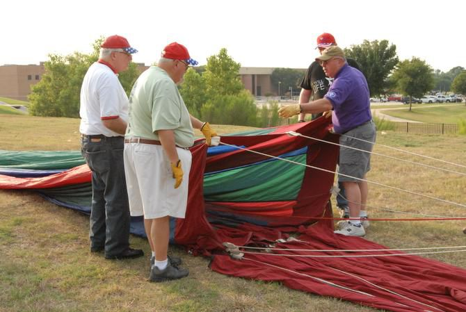 Cannon instructs (from left) John McGill, Tony Casteel and Pat Davis on their roles in getting the balloon up at the recent media preview for the Highland Village Balloon Festival 2014, which will take place this weekend.