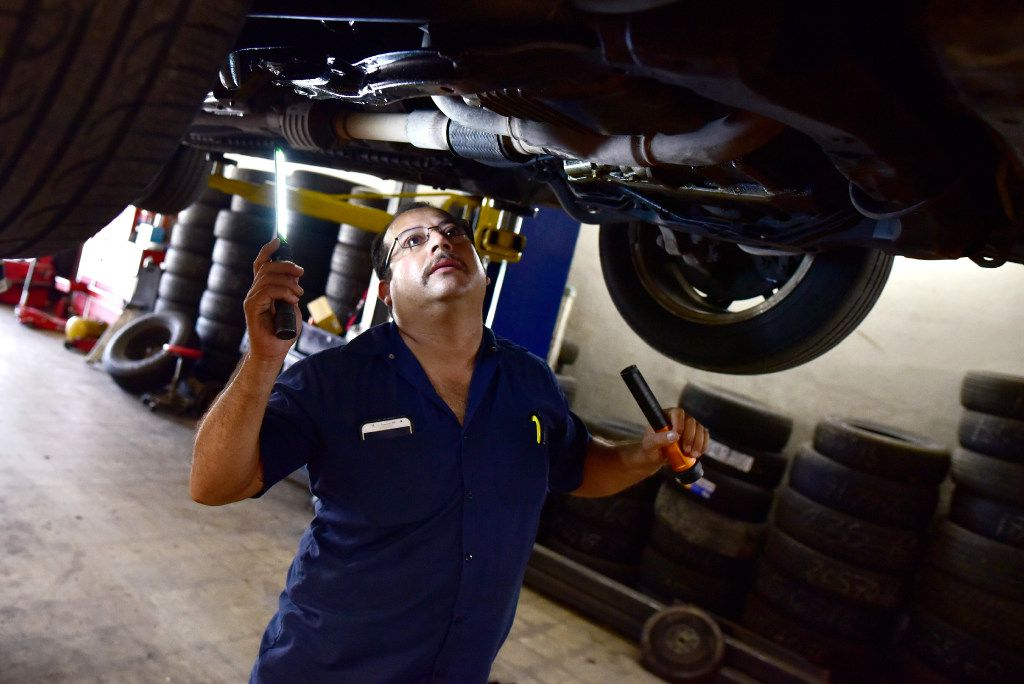 Joaquin Godinez inspects a car for a leak at his auto mechanic shop in southeast Dallas.