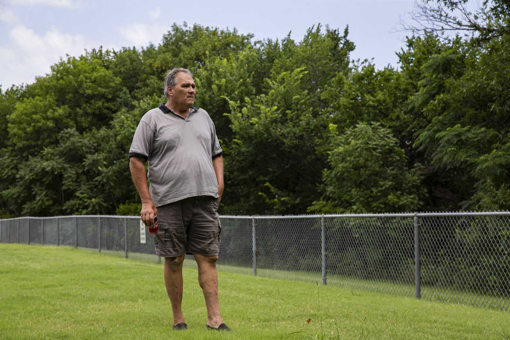 Community activist Don Phillips looks at the fence separating Park Crest Elementary School from Stream 2C4 on Monday, July 12, 2021, in Garland. (Juan Figueroa/The Dallas Morning News)