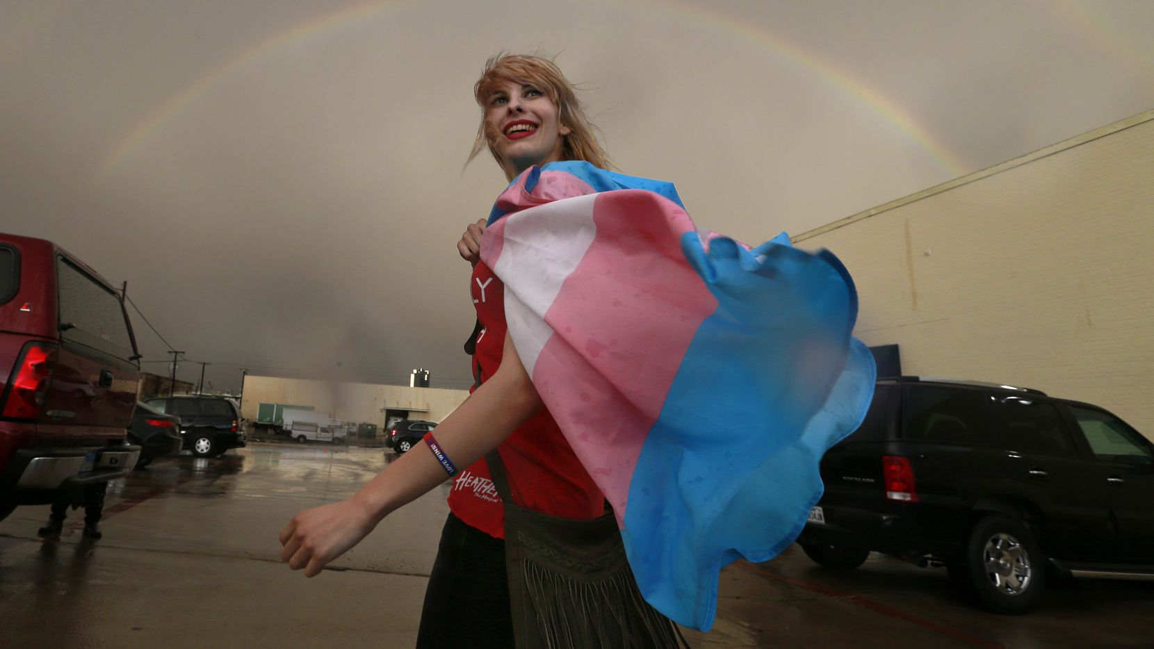Following a public Fort Worth ISD meeting, at which transgender policies in schools were discussed, Alison Francis of Hurst smiles as a full rainbow appears over the Fort Worth ISD Board of Education complex in Fort Worth.  She said she is part of a transgender couple. Earlier Lt. Gov. Dan Patrick addressed the media on Fort Worth Superintendent Kent Scribner's policy to allow transgender students comfortable access to bathrooms.