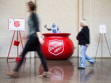 """A tiny cut out version of Ezekiel Elliott mimics a """"bell ringer"""" inside the Salvation Army red kettle at North Park Center."""