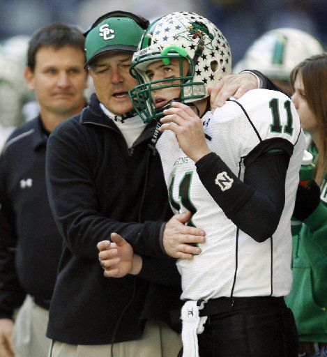 In this photo from 2006, Southlake Carroll's head coach Todd Dodge congratulates his son and quarterback Riley Dodge (11) after Riley threw a touchdown in a playoff game against Colleyville Heritage. The two will face off this weekend as rival coaches.