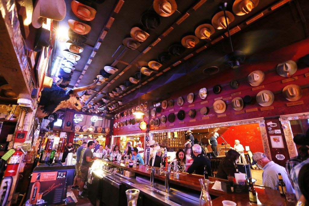 Cowboy hats decorate the ceiling and walls as patrons socialize at the White Elephant Saloon in the Fort Worth Stockyards, Friday, April 3, 2015.