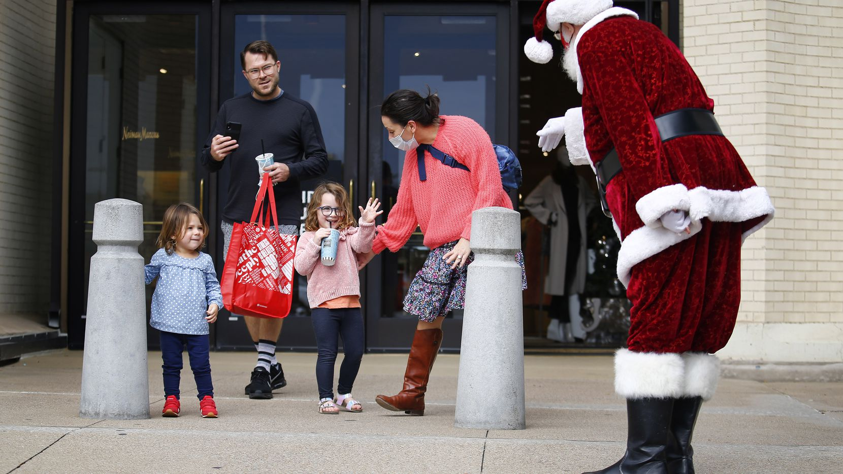 Stella Helt, 4, waves to Santa Claus, aka Mike Davis, as she and her sister, Evie, dad Bob and mom Gayle exit the Neiman Marcus store at NorthPark Center in Dallas, Saturday, November 28, 2020. Despite the COVID-19 pandemic, Santa is maintaining a busy social schedule for the holiday season, with scheduled appearances in Irving and throughout North Texas.