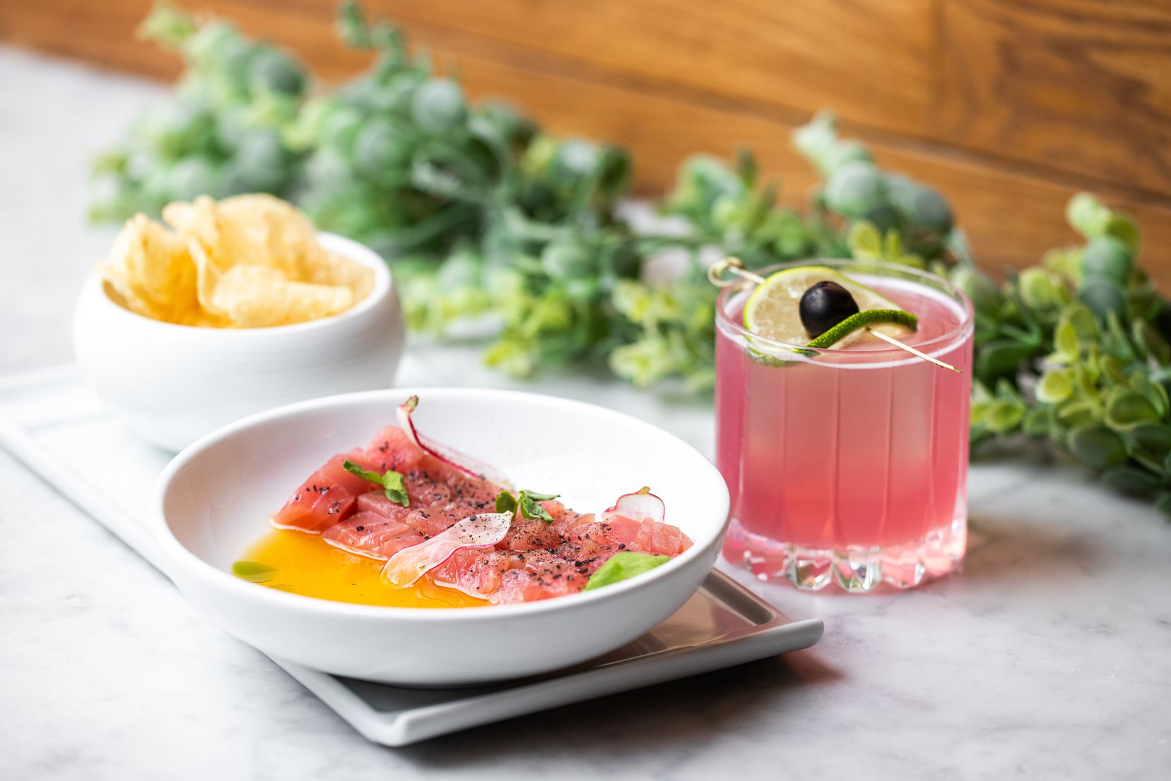 Dinner at Saint Ann in Dallas could mean tuna crudo with a cocktail to match. The pink drink is the Flamingo: rum, lime juice, maraschino cherry liqueur and desert pear syrup.