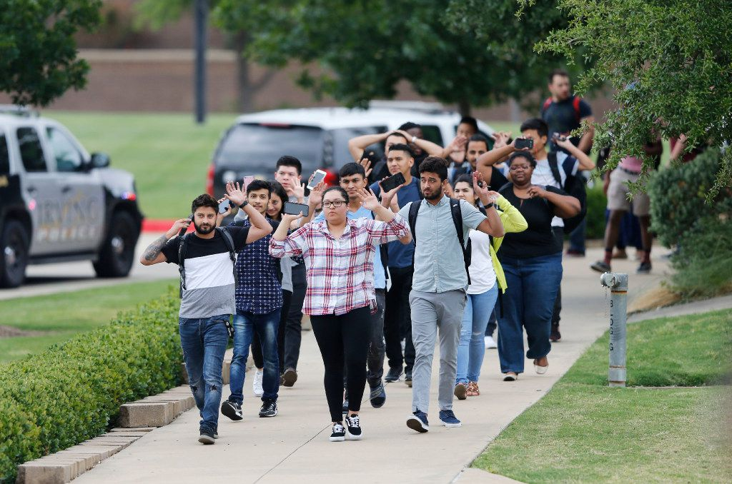 Students and faculty exit a building with their hands up.