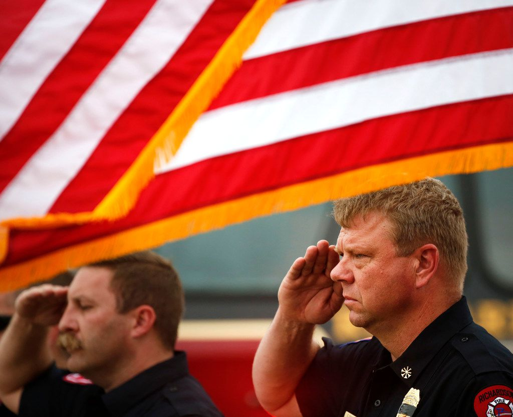 Richardson Fire Asst. Chief Gene Senter salutes during a funeral procession for Dallas police Officer Rogelio Santander on North Central Expressway and Galatyn Parkway in Richardson, Texas on Tuesday, May 1, 2018. Santander was shot and killed last week while trying to arrest a man at a Home Depot.