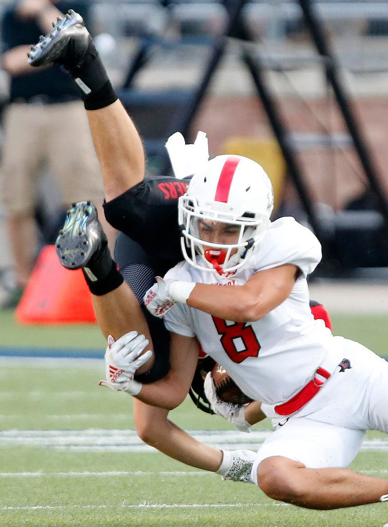 Colleyville Heritage High School running back Braxton Ash (29) is upended by Lovejoy High School cornerback Ryan Scott (8) during the first half as Colleyville Heritage High School hosted Lovejoy High School as part of the Tom Landry Classic at Eagle Stadium in Allen on Saturday, August 31, 2019. (Stewart F. House/Special Contributor)