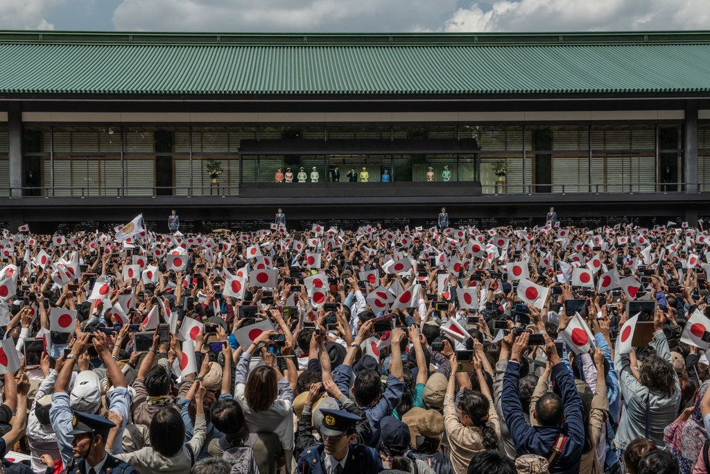 People wave Japanese flags as Emperor Naruhito of Japan waves to members of the public as his wife, Empress Masako, and other members of the Japanese royal family stand beside him on the balcony of the Imperial Palace on May 4, 2019 in Tokyo. Emperor Naruhito has made his first official public appearance following his ascension to the Chrysanthemum Throne last week after his father abdicated citing ill health.