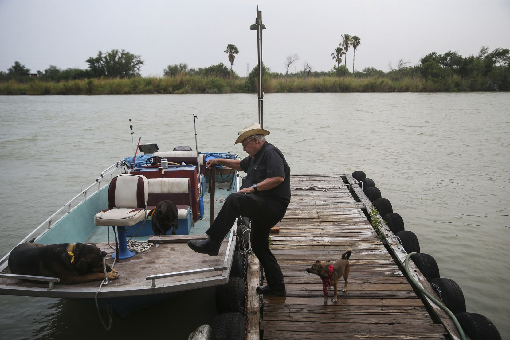 Father Roy Snipes boards his river boat before going out on the Rio Grande.