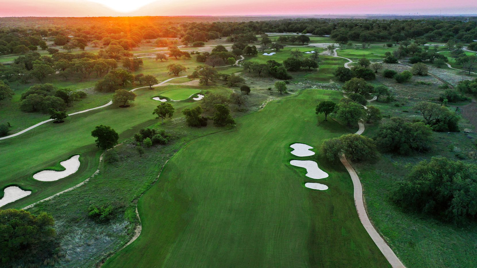 As the sun rises over Driftwood Golf and Ranch Club, several holes on the grassed-in front nine are visible. The holes primarily pictured are Holes 4 & 5 fairway (5 fairway and green on the left, No. 4 fairway and tees on the right). Holes 3 & 6 can be seen at the top of the image.