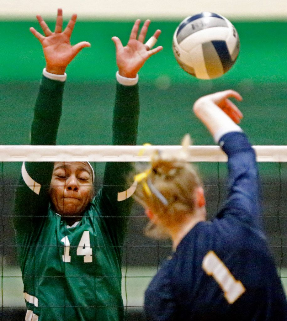 Highland Park High School middle hitter Avery Hellmuth (1)  tries to get a hit past Lebanon Trail High School outside hitter Rayna Williams (14) during game one as Lebanon Trail High School played Highland Park High School in a Class 5A Region II quarterfinal match played at Richardson Berkner High School on Monday night, November 12, 2019. (Stewart F. House/Special Contributor)