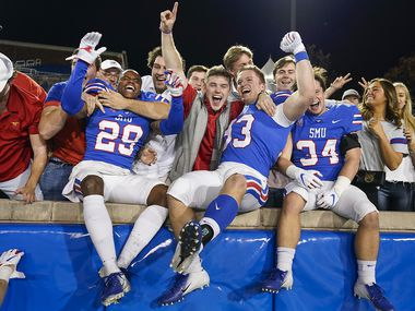 SMU cornerback Justin Guy-Robinson (29), place kicker Kevin Miles (93) and safety Brice Madison (34) celebrate with fans after a 37-20 victory over Tulane in an NCAA football game at Ford Stadium on Saturday, Nov. 30, 2019, in Dallas.