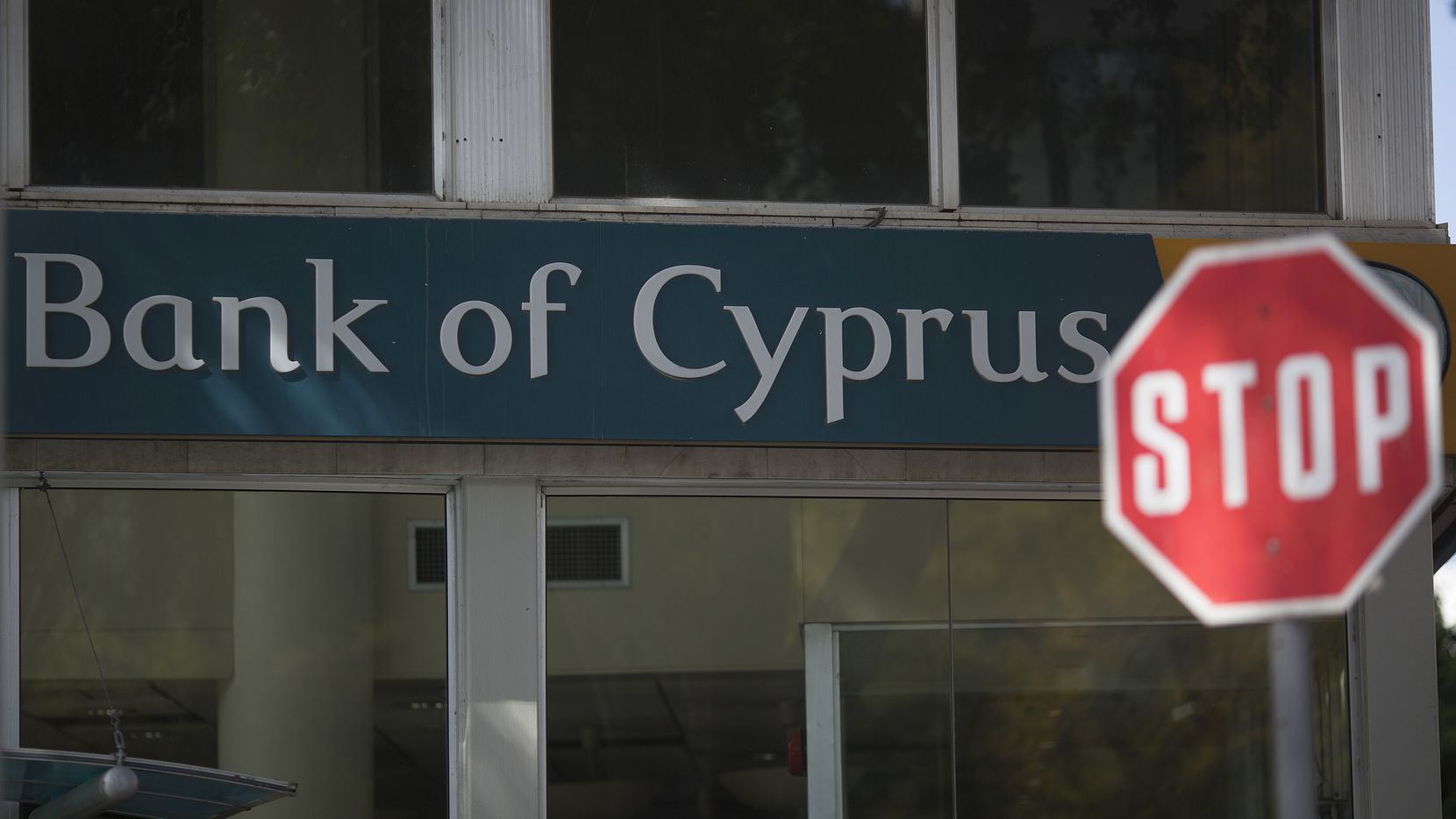 """A road traffic """"Stop"""" sign stands outside a Bank of Cyprus Plc branch in Limassol, Cyprus, on Wednesday, March 27, 2013. The ECB said on March 25 it won't stop the Cypriot central bank from providing the island's banking sector with emergency funding. Photographer: Simon Dawson/Bloomberg via Getty Images"""
